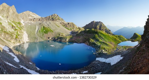Scenic mountain landscape. Lakes in the Caucasus Mountains, Arkhyz. Beautiful water color, snow and blue sky.