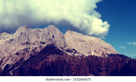 Scenic mountain landscape, mountain peaks,trees in the foreground,limestone rocks,blue sky,clouds,Early autumn,Alps,Austria.