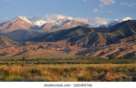 Scenic mountain landscape at sunset with soft light on glacier peaks and blue sky, south shore of lake Issyk Kul, Kyrgyzstan.