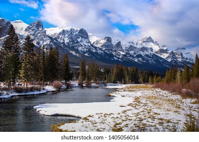 A Scenic Mountain Range View in Canmore Alberta Canada With a Blue Cloudy Sky, Snow, River, Trees and Grasses