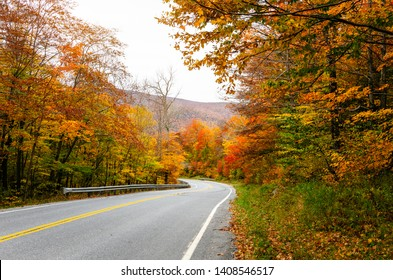 Scenic mountain road through a colourful maple tree forest in autumn. Countryside of Vermont, USA.