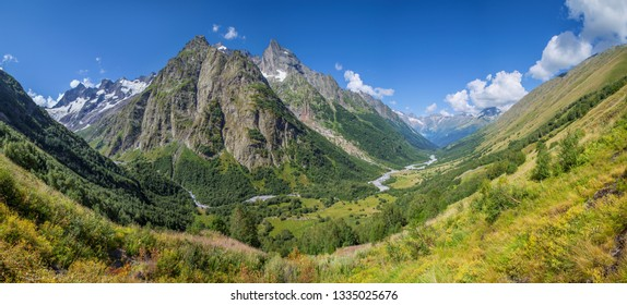 Scenic mountain valley in the Caucasus Mountains, summer greens and snow-capped peaks