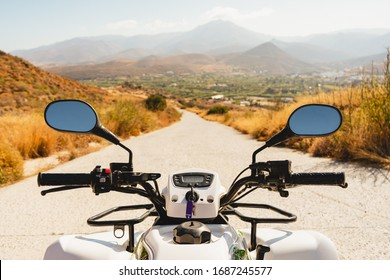 Scenic mountains nature landscape photo from ATV quad bike handlebar POV shot. driving along mountain slope road. tourist having fun during summer vacation outdoor activity concept.