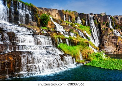 Scenic natural cascades of waterfall with crystal clear water in summer. Amazing sunny landscape in Vietnam. The Pongour waterfall (PonGour) is a popular tourist destination of Asia.