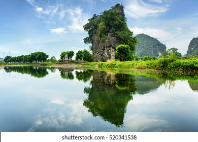 Scenic natural karst tower reflected in water of the Ngo Dong River at the Tam Coc portion, Ninh Binh Province, Vietnam. The Tam Coc is a popular tourist attraction in Asia.