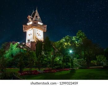 Scenic night view of famous Grazer Uhrturm (clock tower) in flower garden on Schlossberg hill under starry sky, Graz, Austria. Uhrturm is a main symbol of Graz. UNESCO World Heritage site