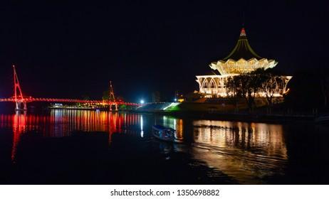 Scenic night view of illuminated State Legislative Assembly and pedestrian bridge. Boat walk by Sarawak river. Waterfront landmarks in Kota Kuching. Popular travel destinations on Borneo in Malaysia.