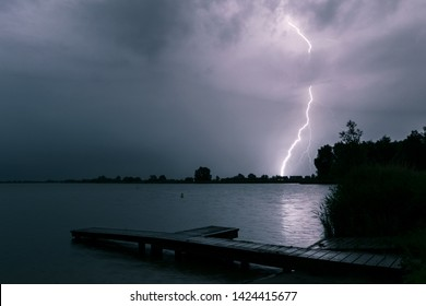Scenic night view of a pier at the shore of a lake while lightning strikes in the background