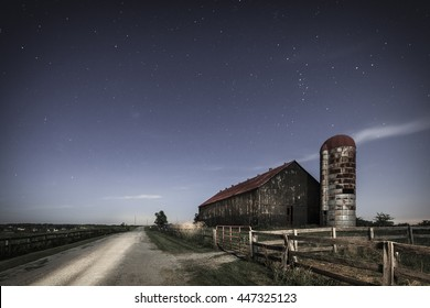 Scenic nighttime image of an old farm barn and a country road in moonlight