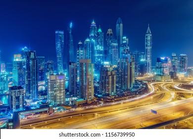 Scenic nighttime skyline of Dubai Marina, UAE. Futuristic skyscrapers of big modern city. Multicolored travel background.