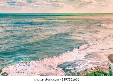 scenic ocean image of waves and surf as a sun setting causes a golden glow. Yachts and sails can be seen on the turquoise water and the waves break on the beach