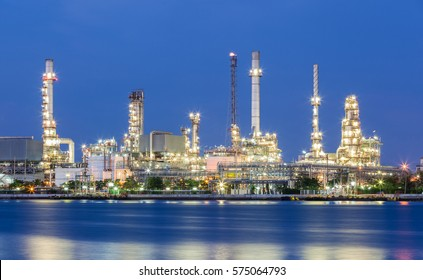 Scenic of oil refinery plant of Petrochemistry industry in twilight time and reflection in near river in Bangkok, Thailand.