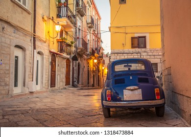 Scenic oldtown street and small retro blue car in Barletta city, Italy