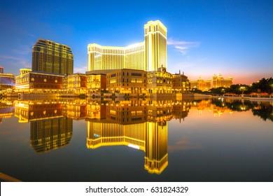 Scenic panorama cityscape of Macau, China, reflected on lake at sunset. Urban night scene.