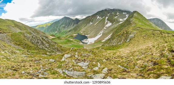 Scenic panorama of mountains in Romania with beautiful mountain lake.