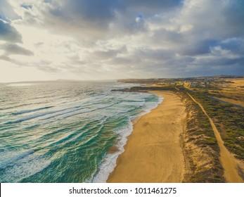 Scenic panorama of ocean coastline with yellow sand beach and rural areas. Kilcunda, Victoria, Australia