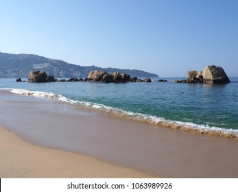 Scenic panorama of rocks at bay of ACAPULCO city in Mexico, Pacific Ocean waves on sandy beach landscapes with clear blue sky in 2018 hot sunny winter day, North America on March.