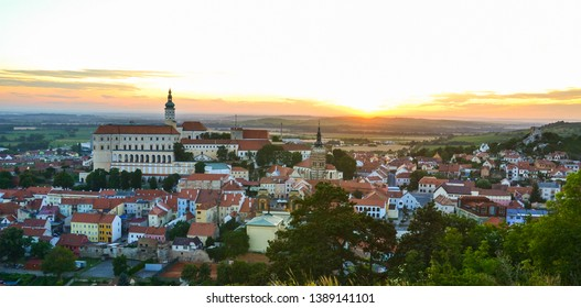 Scenic panorama romantic view of beautiful historical landmark Mikulov Castle and historical city centre, sunset light. View from the Holy hill above Mikulov,Moravia, Czech Republic.Old European town.