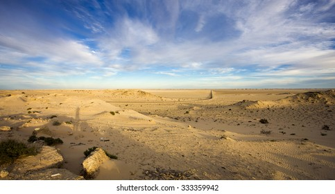 Scenic panorama of sand dunes and straight road on the Ad Dakhla peninsula in South of Morocco.