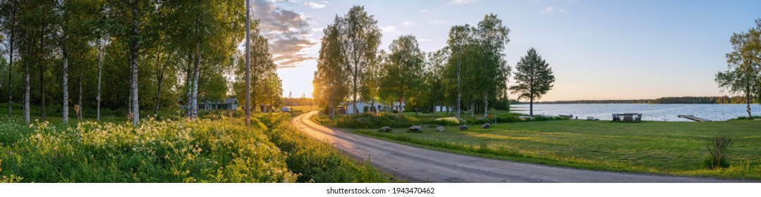 Scenic panorama of Swedish birch forest, summer village, lake and beautiful Sunset lighting on countryside road. Sweden.