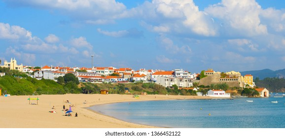 Scenic panorama of traditional village and people relaxing on river beach. Vila de Milfontes, Alentejo, Portugal