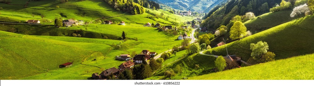 Scenic panoramic landscape of a picturesque green mountain valley in spring. Historic village with blossoming trees and traditional houses. Germany, Black Forest. Colourful travel background.