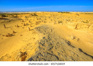 Scenic panoramic landscape of Pinnacles Desert inside Nambung National Park, near Cervantes, Western Australia. The desert consists of Pinnacles, bizarre limestone rock formations. Sunny day blue sky.