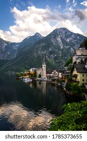 Scenic panoramic view of famous Hallstatt lakeside town reflecting in Hallstattersee lake in the Austrian Alps in scenic morning light on a beautiful sunny day in summer, Salzkammergut region, Austria