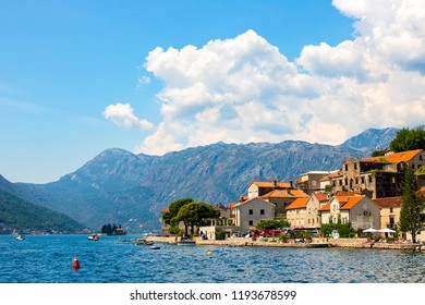Scenic panoramic view of the historical city of Perast, located in the Bay of Kotor on a sunny day with blue sky and white clouds in summer, Montenegro, southern Europe