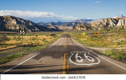 Scenic panoramic view of long straight road on famous Route 66 with historical street signs and paintings in classic american wild western mountain scenery in beautiful golden evening light at sunset