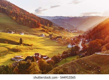 Scenic panoramic view of a picturesque mountain valley in autumn at sunset. Colourful countryside landscape with mountain forests, traditional houses and old monastery. Germany, Black Forest.