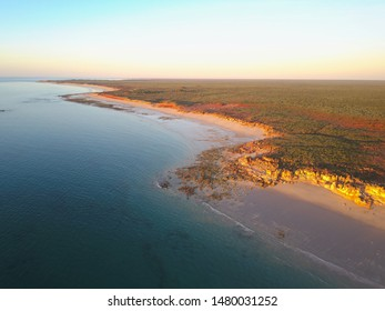 Scenic panoramic view of remote coast near Broome, Western Australia, with  ocean beach, cliffs, outback landscape, sunset sky and horizon as copy space.