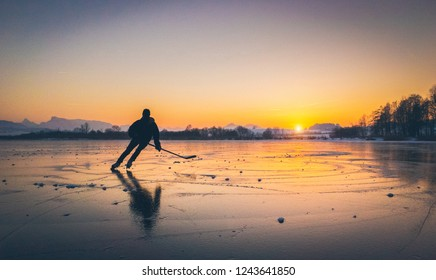 Scenic panoramic view of the silhouette of a young hockey player skating on a frozen lake with amazing reflections in beautiful golden evening light at sunset in winter