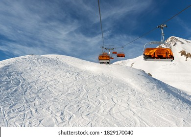 Scenic panoramic view of Silvretta ski area at Iscgl and Samnaun skiing resort with chairlifts , downhill slpoes and clear blue sky on background. Winter sport travel recreation and activities