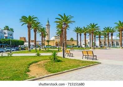 The scenic park with palms in front of Ribat fortress, the mosque of Habib Bourguiba is seen behind the trees, Monastir, Tunisia.