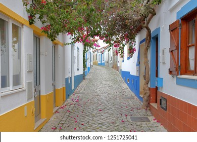 A scenic paved alley with colorful houses and flowers in the fishing village of Ferragudo, Algarve, Portugal