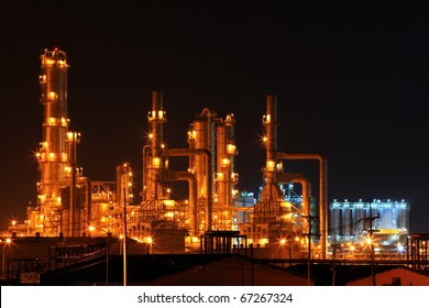 scenic of petrochemical oil refinery plant shines at night, closeup