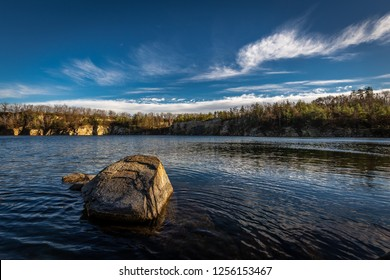 Scenic photo of flooded quarry near Masovice, Znojmo, Czech Republic with roc in the foreground and dark blue sky with white clouds