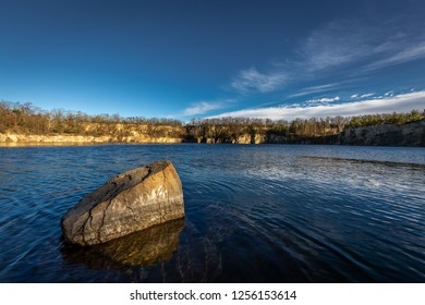 Scenic photo of flooded quarry near Masovice, Znojmo, Czech Republic with dark blue sky and white clouds