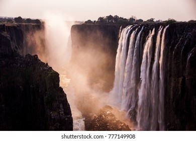 scenic picture of the victoria falls  photographed by sunset with red colors and some rocks and grass in the front of the picture