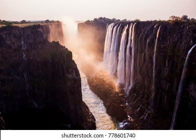scenic picture of the victoria falls  photographed by sunset with red colors and some rocks and grass in the front of the picture (4)