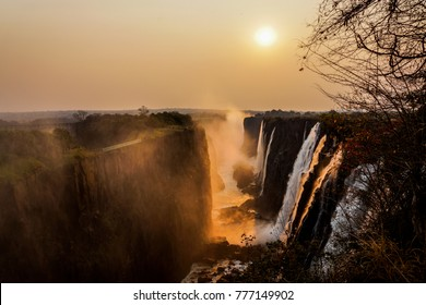 scenic picture of the victoria falls and the zambezi canyon below photographed by sunset with red colors and some rocks and grass in the front of the picture