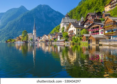 Scenic picture-postcard view of famous Hallstatt lakeside town reflecting in Hallstattersee lake in the Austrian Alps in beautiful morning light on a sunny day in summer, Salzkammergut region, Austria
