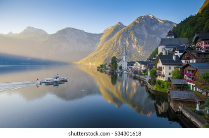 Scenic picture-postcard view of famous Hallstatt lakeside village in the Austrian Alps with passenger ship in beautiful morning light at sunrise on a sunny day in summer, Salzkammergut region, Austria
