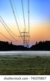 Scenic power line with rising fog on a field with forest in background and colorful dusk sky.