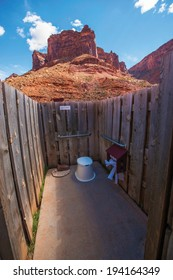 Scenic Primitive Restroom with the View. Simple Wood Wall Camping Restroom Between Scenic Rock Formations.