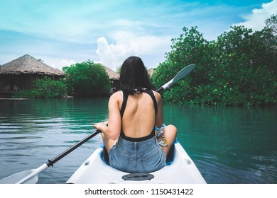 Scenic rear view of sexy young girl kayaking on the lake during summer holidays vacation