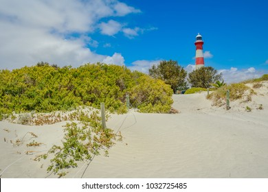 Scenic red and white Moore Lighthouse Point on blue sky in Geraldton, Western Australia, from pristine beach with dunes The historic steel tower is built in 1878. Iconic landscape in Geraldton.