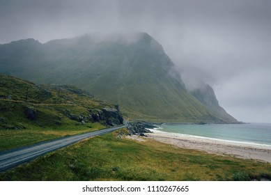 Scenic road along the coastline and high mountains in Norway on a rainy and foggy day