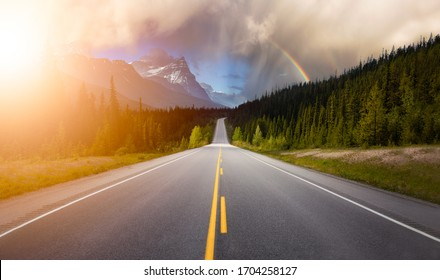 Scenic road in the Canadian Rockies during a vibrant sunny summer day with Rainbow. Rainy Sky Composite. Taken in Icefields Parkway, Banff National Park, Alberta, Canada.